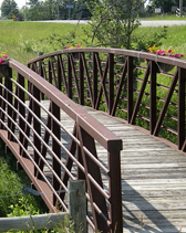 Brown walking bridge over a creek with pink flowers hanging from the rails
