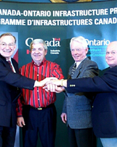 Group of men celebrating the receipt of infrastructure funding