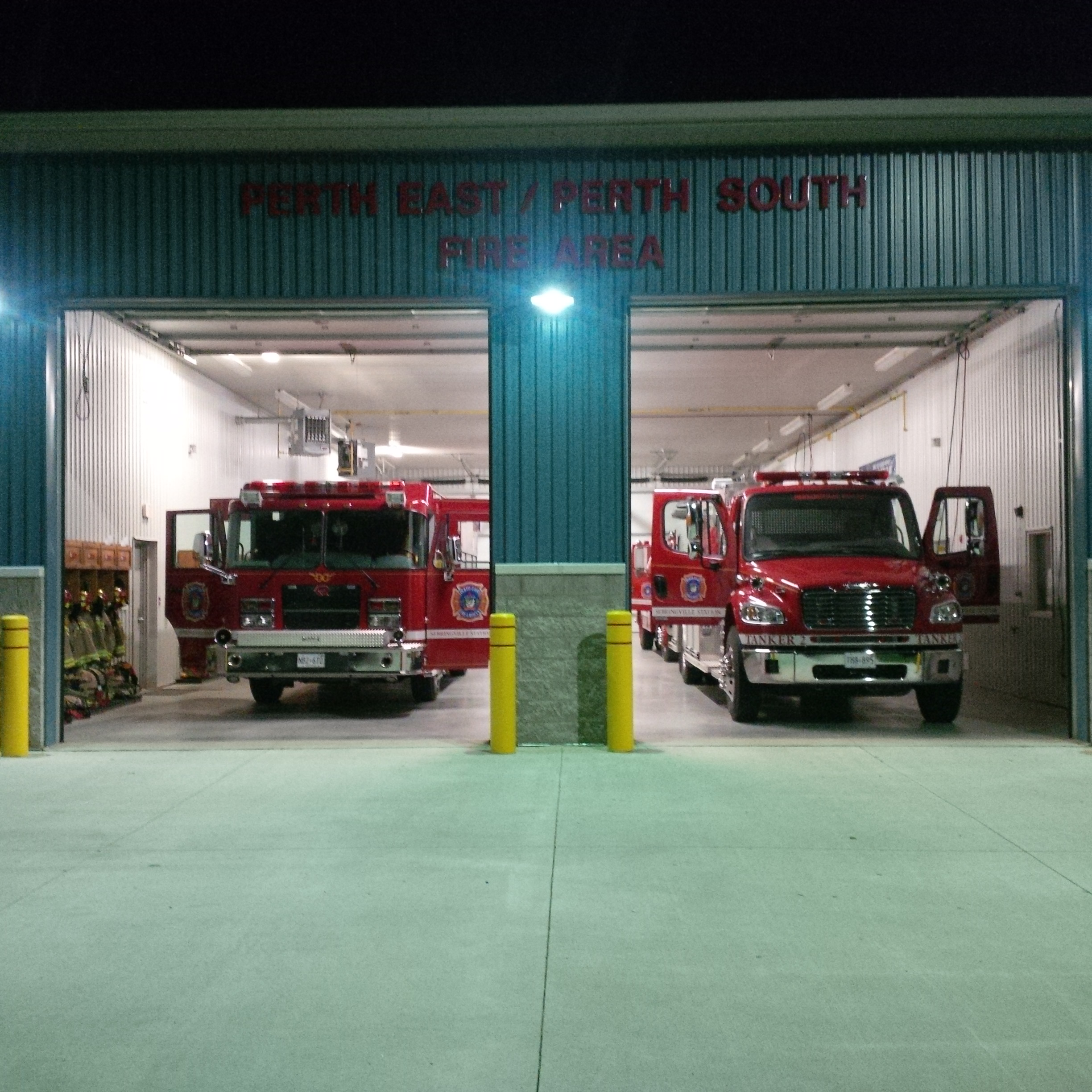 Fire station with its bay doors open and fire trucks parked inside at the Sebringville Fire Station.