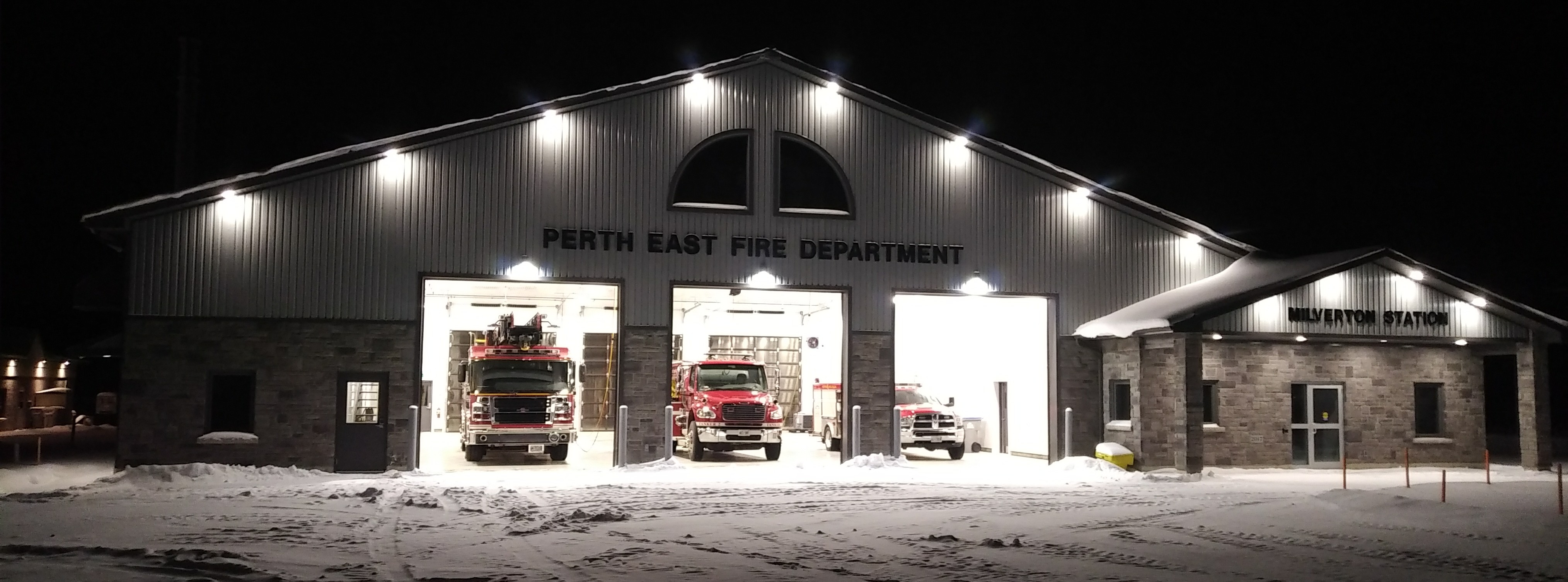 Fire station with the 3 bay doors open and trucks sitting inside