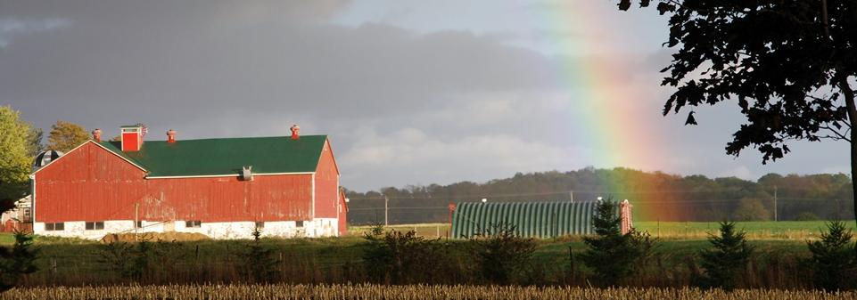 Red barn surrounded by fields with a rainbow