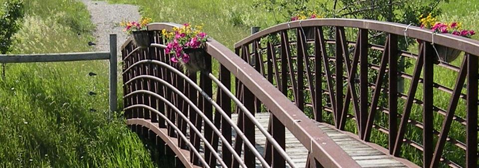 Walking bridge over creek with gravel path and flowers